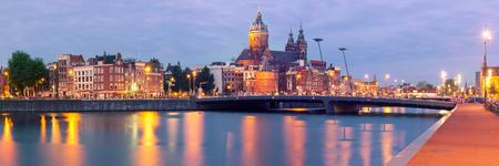 Night panoramic city view of Amsterdam canal, bridge and Basilica of Saint Nicholas, Holland, Netherlands. Long exposure. Used toning