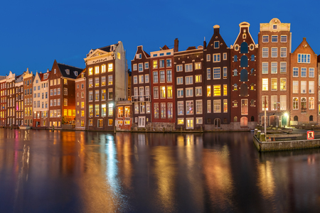 Beautiful typical Dutch dancing houses at the Amsterdam canal Damrak at night, Holland, Netherlands.