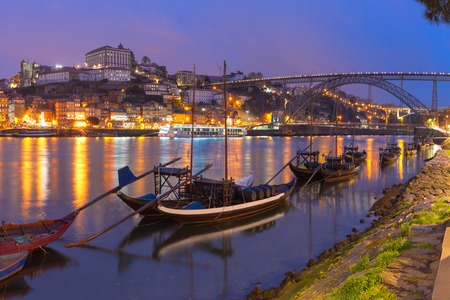 rabelo: Traditional rabelo boats with barrels of Port wine on the Douro river, Ribeira and Dom Luis I or Luiz I iron bridge on the background, Porto, Portugal.