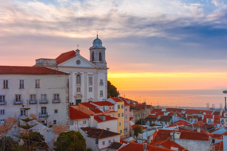 View of Alfama, the oldest district of the Old Town, with Church of Saint Stephen at cloudy sunrise, Lisbon, Portugal