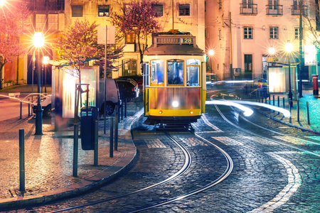 Famous vintage yellow 28 tram of of Alfama, in the oldest district of the Old Town, at night, Lisbon, Portugal 版權商用圖片