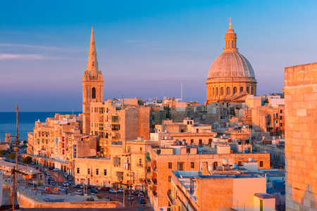 View from above of the domes of churches and roofs at beautiful sunset with churches of Our Lady of Mount Carmel and St. Pauls Anglican Pro-Cathedral, Valletta, Capital city of Malta
