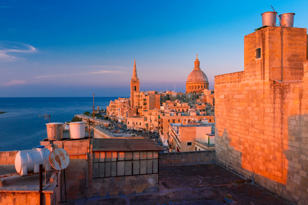 View from above of the domes of churches and roofs at beautiful sunset with church of Our Lady of Mount Carmel and St. Pauls Anglican Pro-Cathedral, Valletta, Capital city of Malta