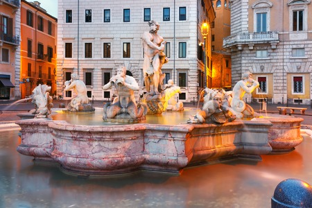 Fontana del Moro with four Tritons sculpted on the famous Piazza Navona Square during morning blue hour, Rome, Italy.