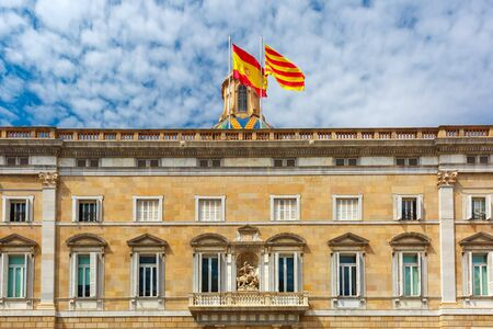 The building of the Government of Catalonia or Generalitat de Catalunya with Catalan and Spain flags on the Placa de Sant Jaume in Old Town of Barcelona, Spain Stock Photo