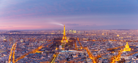 Paris, France - December 26, 2016: Aerial panoramic view of Paris skyline with Shimmering Eiffel Tower and business district of Defense at pink sunset, as seen from Montparnasse Tower