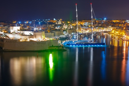 Aerial skyline view of ancient defences of Birgu and Fort St. Angelo, as seen from Valletta at night, Malta.