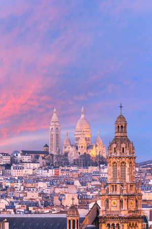Aerial view of Sacre-Coeur Basilica or Basilica of the Sacred Heart of Jesus at the butte Montmartre and Saint Trinity church at nice sunset, Paris, France Imagens