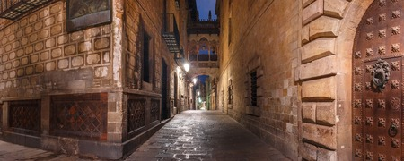 Panorama of cobbled medieval Carrer del Bisbe street with Bridge of Sighs in Barri Gothic Quarter at night, Barcelona, Catalonia, Spain Stock Photo