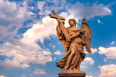Marble statue of Angel with the Cross at sunset, one of the ten angels on Saint Angel Bridge, symbols of Christs Passion, Rome, Italy