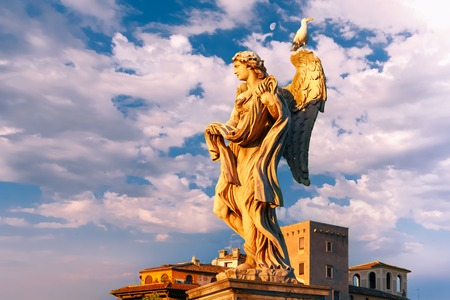 Marble statue of Angel with the Garment and Dice at sunset, one of the ten angels on Saint Angel Bridge, symbols of Christs Passion, Rome, Italy Archivio Fotografico