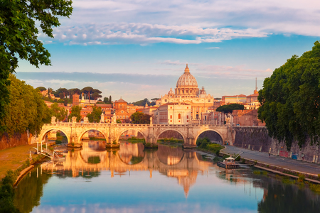 Saint Angel bridge and Saint Peter Cathedral with a mirror reflection in the Tiber River in the sunny morning in Rome, Italy.