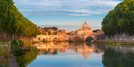 Panorama of Saint Angel bridge and Saint Peter Cathedral with a mirror reflection in the Tiber River in the sunny morning in Rome, Italy.
