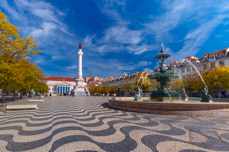 Rossio square with wavy cobble stone pattern, fountain and monument of Pedro IV in Lisbon, capital of Portugal