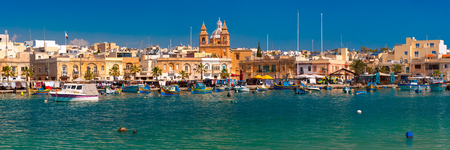 Panorama with traditional eyed colorful boats Luzzu in the Harbor of Mediterranean fishing village Marsaxlokk, Malta