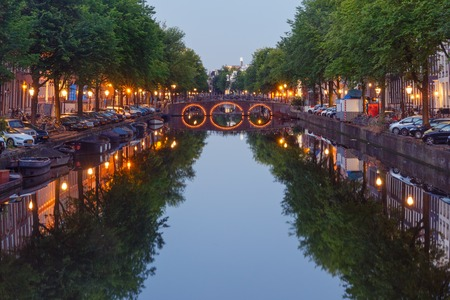 Amsterdam canal, bridge and typical houses, boats and bicycles during morning blue hour, Holland, Netherlands. Used toning