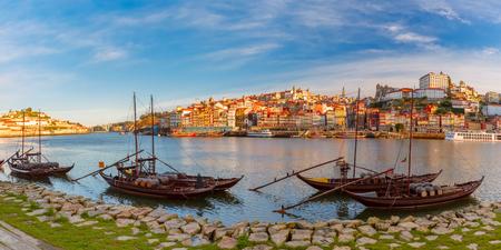 Vista panorámica de los barcos tradicionales del rabelo con los barriles de vino de Oporto en el río del Duero, Ribeira en el fondo, Oporto, Portugal. Foto de archivo