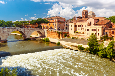 View of the Tiber island or Isola Tiberina with Pons Cestius and Basilica of St Bartholomew in sunny day, Rome, Italy Stock Photo