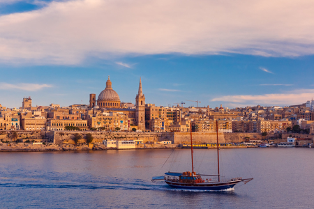Valletta Skyline with ship at beautiful sunset from Sliema with churches of Our Lady of Mount Carmel and St. Pauls Anglican Pro-Cathedral, Valletta, Capital city of Malta Stock Photo