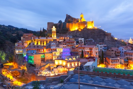 Amazing View of Narikala ancient fortress with St Nicholas Church, Jumah Mosque, Sulphur Baths and famous colorful balconies in old historic district Abanotubani in night Illumination during morning blue hour, Tbilisi, Georgia. Stock Photo