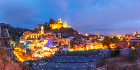 Amazing panoramic view of Narikala ancient fortress with St Nicholas Church, Jumah Mosque, Sulphur Baths and famous colorful balconies in old historic district Abanotubani in night Illumination during morning blue hour, Tbilisi, Georgia.