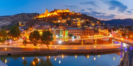 Amazing panoramic view of Olt town with Narikala ancient fortress, St Nicholas Church and Kura river in night Illumination during evening blue hour, Tbilisi, Georgia. Stock Photo