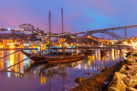 Traditional rabelo boats with barrels of Port wine on the Douro river, Ribeira and Dom Luis I or Luiz I iron bridge on the background, Porto, Portugal.
