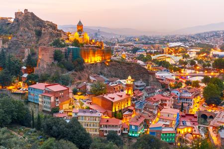 Narikala, Jumah-moskee, Zwavelbaden en beroemde kleurrijke balkons in oud historisch district Abanotubani in nachtverlichting bij zonsondergang, Tbilisi, Georgië.