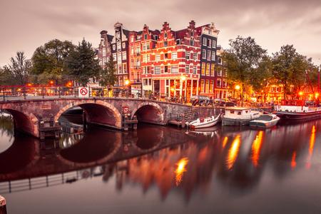 Амстердам канал, мост и типичные дома, лодки и велосипеды в вечерние сумерки синий час, Голландия, Нидерланды. Б тонировка