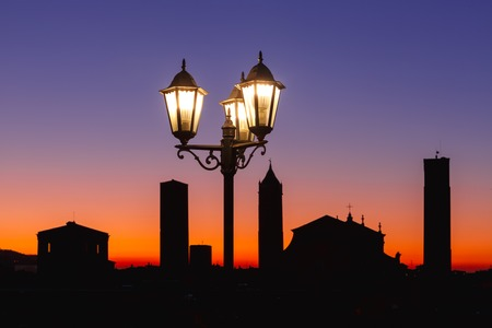Night aerial view of Bologna Cathedral and towers of Old Town in medieval city Bologna with vintage beautiful lantern at sunset, Emilia-Romagna, Italy