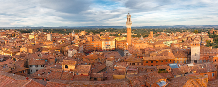 Panoramic aerial view of Mangia Tower or Torre del Mangia towering above of the Palazzo Pubblico on Piazza del Campo in medieval city of Siena in the cloudy day, Tuscany, Italy