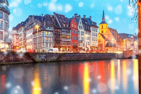 Pátio de Natal pitoresco e igreja de São Nicolau com reflexos de espelho no rio Ile durante a hora azul da noite, Estrasburgo, Alsácia, França