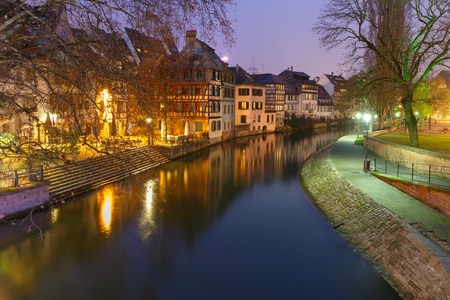 Traditional Alsatian half-timbered houses and canal in Petite France during twilight blue hour, Strasbourg, Alsace, France