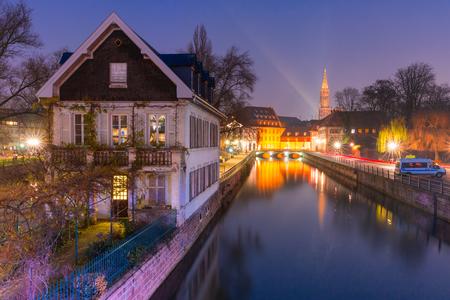 小柄なフランスの伝統的なアルザスの半木造住宅、朝の青い時間の間に橋と川の堤防Ile、背景にストラスブール大聖堂、ストラスブール、アルザス
