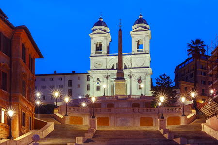 Monumental stairway Spanish Steps, seen from Piazza di Spagna, and Trinita dei Monti church during morning blue hour, Rome, Italy.