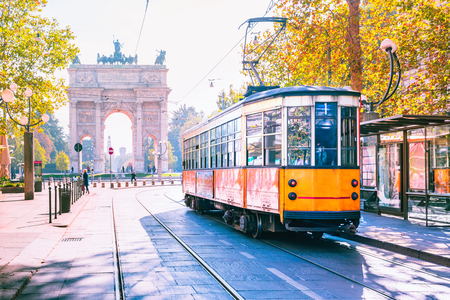 Famous vintage tram in the centre of the Old Town of Milan in the sunny day, Lombardia, Italy. Arch of Peace, or Arco della Pace on the background. Фото со стока