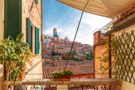 Beautiful view of Dome and campanile of Siena Cathedral, Duomo di Siena, and Old Town of medieval city of Siena in the sunny day through autumn leaves, Tuscany, Italy Stock Photo