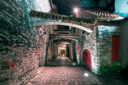 Medieval street St. Catherines Passage or Katariina kaik, half-hidden walkway in Old Town at night, Tallinn, Estonia