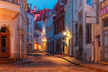 Beautiful illuminated medieval street in Old Town of Tallinn during evening blue hour, Estonia Stock Photo