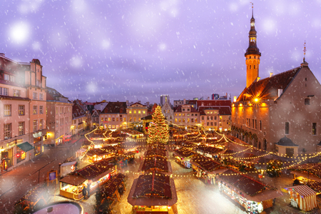 Decorated and illuminated Christmas tree and Christmas Market at Town Hall Square or Raekoja plats at snowy winter night, Tallinn, Estonia. Aerial view