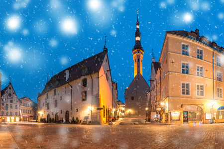 Beautiful illuminated street of Medieval Old Town and Town Hall at snowy winter night, Tallinn, Estonia