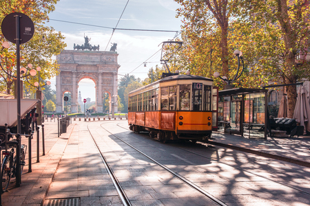 Famous vintage tram in the centre of the Old Town of Milan in the sunny day, Lombardia, Italy. Arch of Peace, or Arco della Pace on the background. Imagens