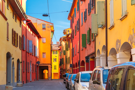 Medieval street portico with bright colored houses in the Old Town in the sunny day, Bologna, Emilia-Romagna, Italy Stock Photo