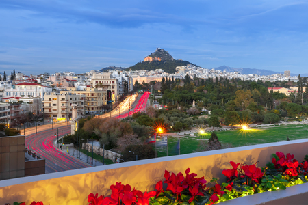 Mount Lycabettus towering above of the roofs of Old Town during evening blue hour in Athens, Greece