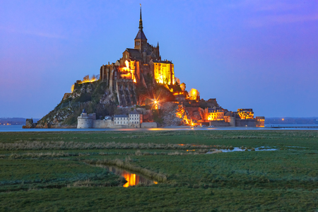 Famous Mont Saint Michel Illuminated in the evening blue hour with reflection in the canal on the water meadows, Normandy, France