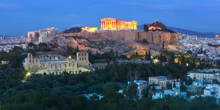 Panoramic aerial view of the Acropolis Hill, crowned with Parthenon during evening blue hour in Athens, Greece