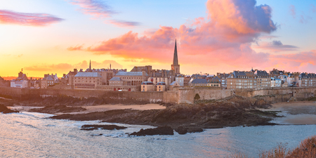 Panoramic view of walled city Saint-Malo with St Vincent Cathedral at sunrise at high tide. Saint-Maol is famous port city of Privateers is known as city corsaire, Brittany, France