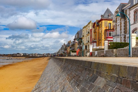 High stone embankment and beach at low tide, in beautiful walled port city of Privateers Saint-Malo, also known as city corsaire, Brittany, France Stock Photo