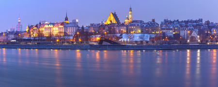 Panoramic view of Old Town with reflection in the Vistula River during evening blue hour, Warsaw, Poland.
