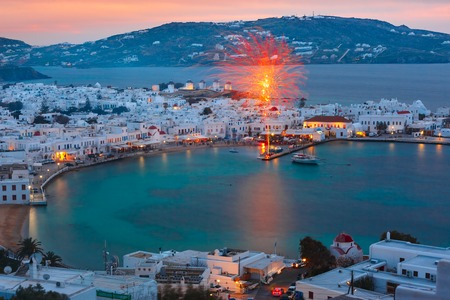 Aerial view of Mykonos City, Chora with Old Port, white houses, windmilles and churches on the island Mykonos, The island of the winds, during evening blue hour, Greece